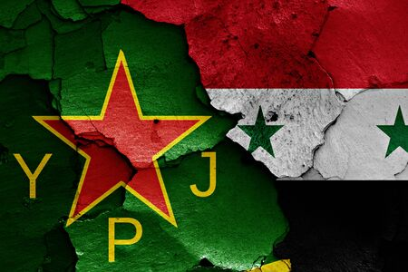 women's issues: flags of YPJ and Syria painted on cracked wall Stock Photo