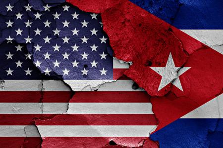 ひびの入った壁に米国とキューバの国旗が描かれました。 写真素材
