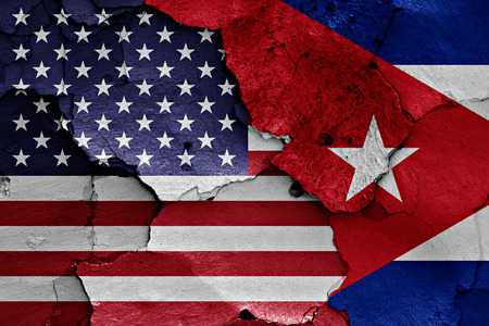 cuba flag: flags of USA and Cuba painted on cracked wall