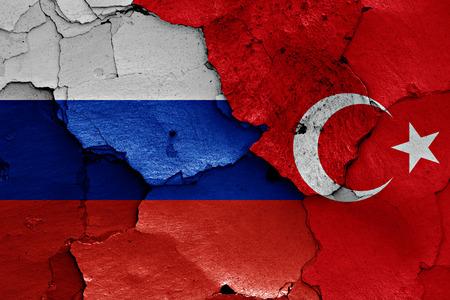 Flaggen von Russland und der Türkei auf gebrochener Wand gemalt
