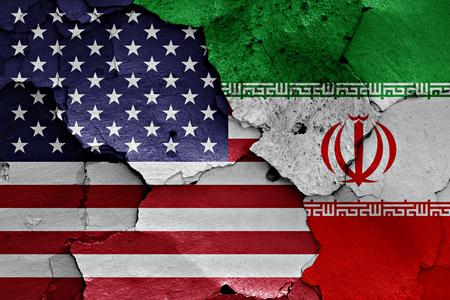 ひびの入った壁に米国とイランの国旗が描かれました。 写真素材