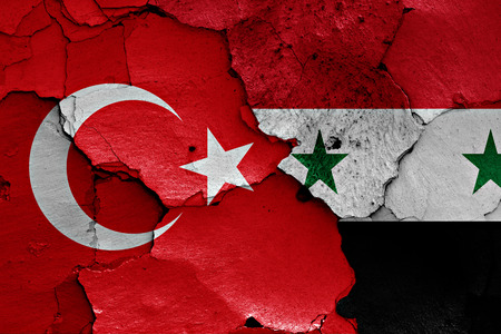 syrian war: flags of Turkey and Syria painted on cracked wall