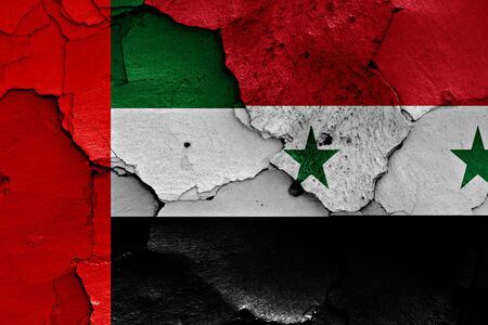 international crisis: flags of United Arab Emirates and Syria painted on cracked wall