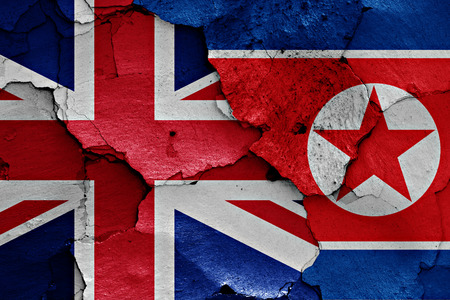 north korea: flags of UK and North Korea painted on cracked wall