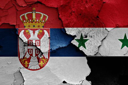 terrorism crisis: flags of Serbia and Syria painted on cracked wall Stock Photo