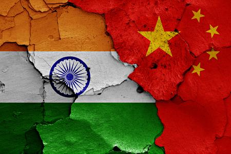 ひびの入った壁にインドと中国の国旗が描かれました。 写真素材