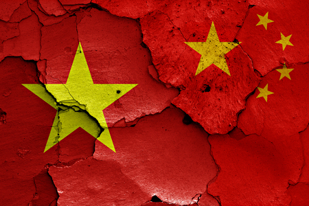 muralla china: flags of Vietnam and China painted on cracked wall Foto de archivo
