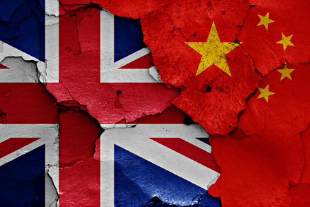 cracked wall: flags of UK and China painted on cracked wall Stock Photo