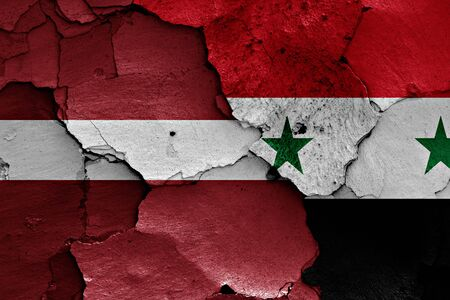 terrorism crisis: flags of Latvia and Syria painted on cracked wall Stock Photo