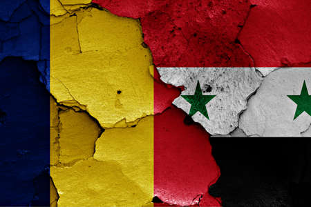 terrorism crisis: flags of Romania and Syria painted on cracked wall Stock Photo