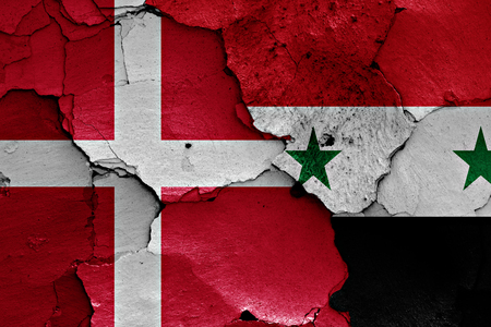 unwelcome: flags of Denmark and Syria painted on cracked wall