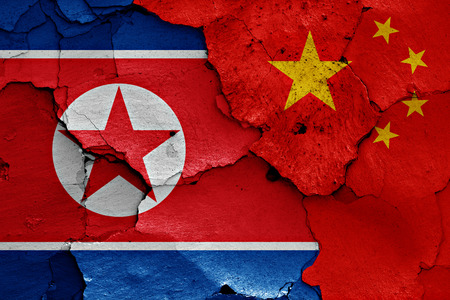 breakup: flags of North Korea and China painted on cracked wall Stock Photo