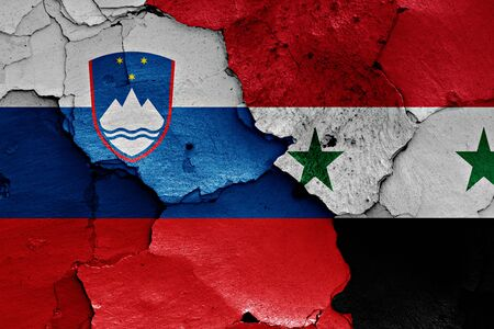 terrorism crisis: flags of Slovenia and Syria painted on cracked wall Stock Photo
