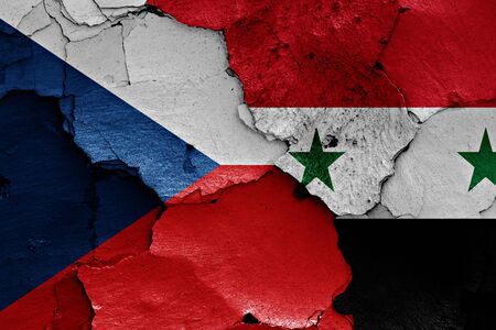 international crisis: flags of Czech Republic and Syria painted on cracked wall