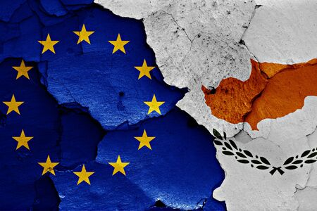 trade off: flags of EU and Cyprus painted on cracked wall Stock Photo