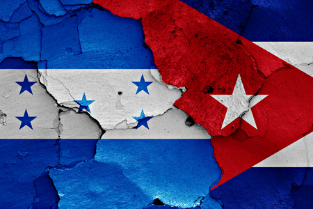 cracked wall: flags of Honduras and Cuba painted on cracked wall Stock Photo
