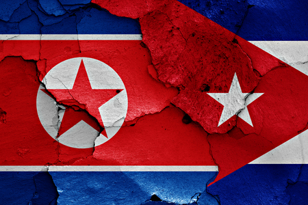bandera de cuba: banderas de Corea del Norte y Cuba pintados en la pared agrietada Foto de archivo