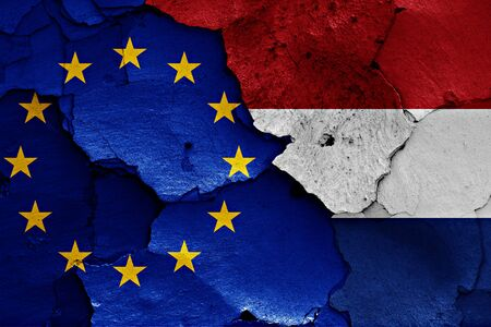 trade off: flags of EU and Netherlands painted on cracked wall