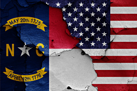 flags of North Carolina and USA painted on cracked wall