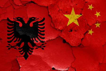 nationalism: flags of Albania and China painted on cracked wall