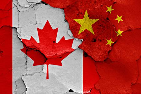 ひびの入った壁にカナダと中国の国旗が描かれました。 写真素材