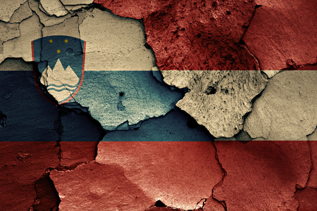 flags of Slovenia and Austria painted on cracked wall Stock Photo