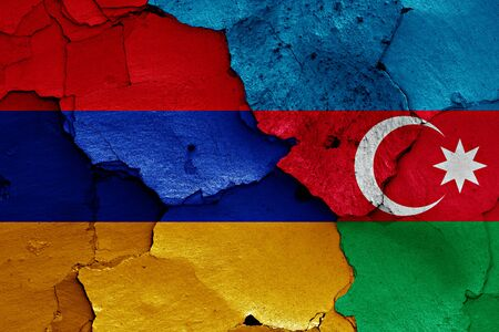 ceasefire: flags of Armenia and Azerbaijan painted on cracked wall