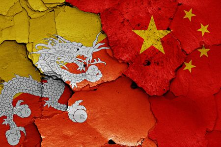 flags of Bhutan and China painted on cracked wall Stock Photo