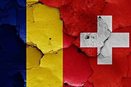 cracked wall: flags of Romania and Switzerland painted on cracked wall
