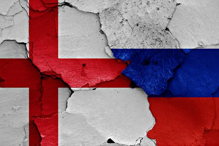 flags of England and Russia painted on cracked wall