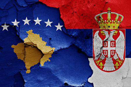 cracked wall: flags of Kosovo and Serbia painted on cracked wall Stock Photo