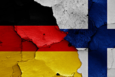 cracked wall: flags of Germany and Finland painted on cracked wall Stock Photo