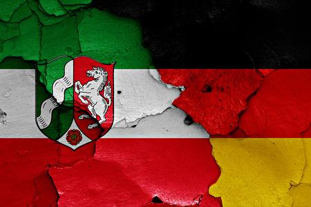 rhine westphalia: flags of North Rhine Westphalia and Germany painted on cracked wall Stock Photo