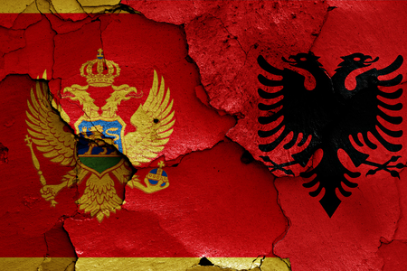 cracked wall: flags of Montenegro and Albania painted on cracked wall Stock Photo