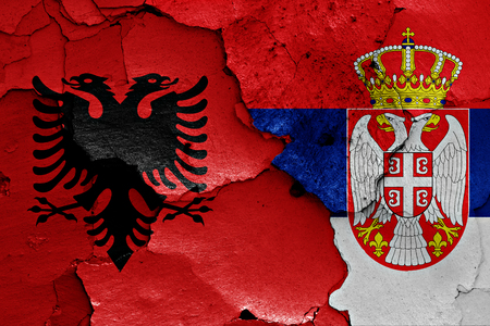 cracked wall: flags of Albania and Serbia painted on cracked wall Stock Photo