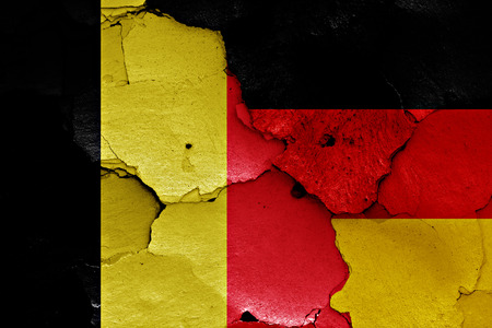 cracked wall: flags of Belgium and Germany painted on cracked wall Stock Photo
