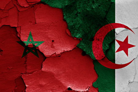 algerian flag: flags of Morocco and Algeria painted on cracked wall