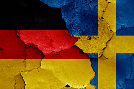 flags of Germany and Sweden painted on cracked wall