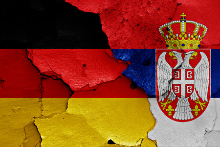flags of Germany and Serbia painted on cracked wall