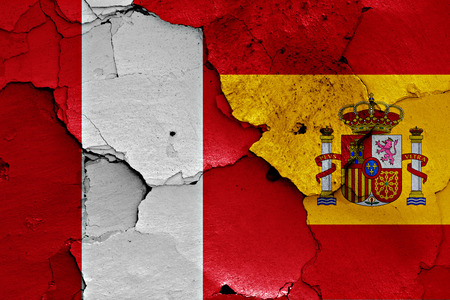 flags of Peru and Spain painted on cracked wall