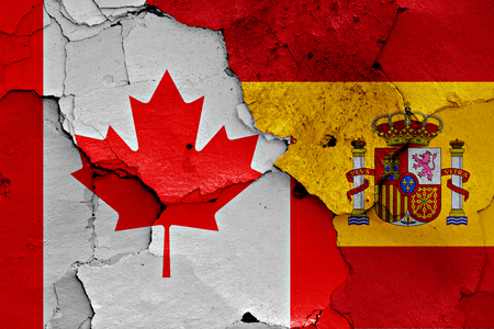 flags of Canada and Spain painted on cracked wall