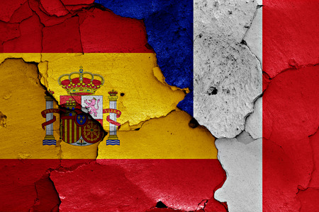 flags of Spain and France painted on cracked wall