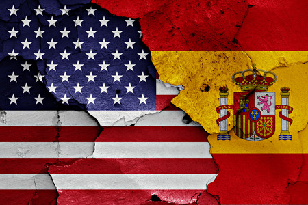 flags of USA and Spain painted on cracked wall