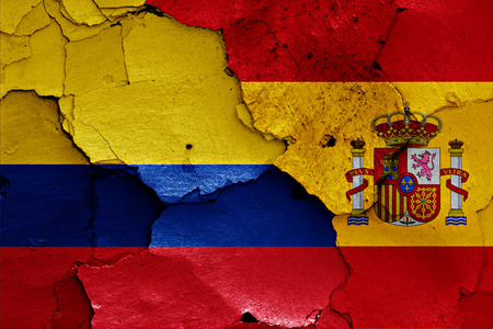 flags of Colombia and Spain painted on cracked wall Foto de archivo