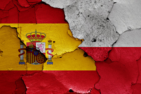 flags of Spain and Poland painted on cracked wall