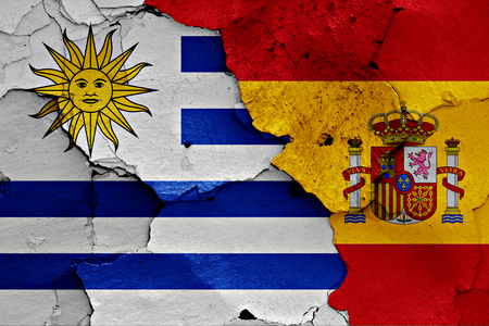 flags of Uruguay and Spain painted on cracked wall Stock Photo