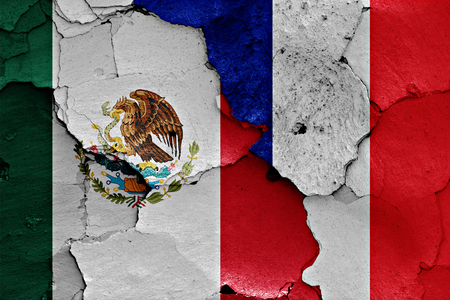 flags of Mexico and France painted on cracked wall Stock Photo