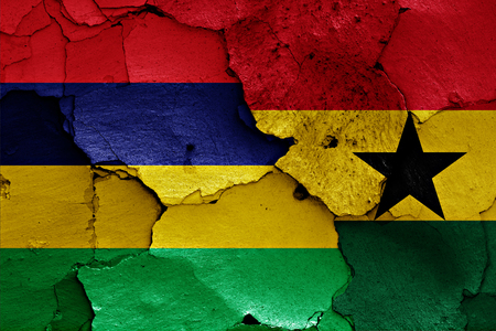 flags of Mauritius and Ghana painted on cracked wall Stock Photo