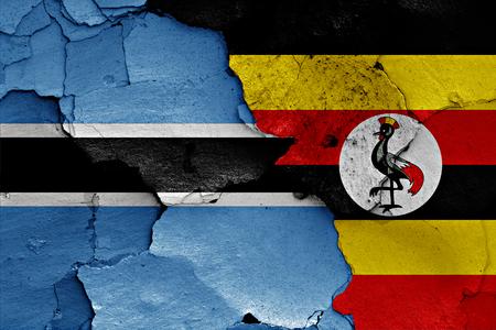 flags of Botswana and Uganda painted on cracked wall