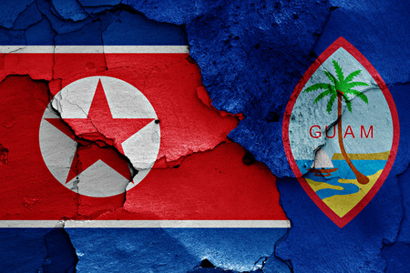 flag of North Korea and Guam painted on cracked wall